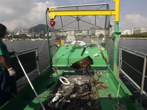 Um trabalhador recolhe lixo coletado por uma barca  na Baía de Guanabara, no Rio de Janeiro, Brasil, segunda-feira (6). (Foto: Silvia Izquierdo/AP)