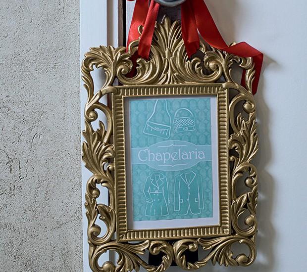 O porta-retrato dourado pendurado na porta indica a localização da chapelaria (Foto: Ricardo Corrêa/Editora Globo)