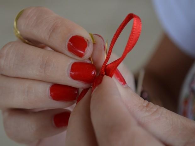 A empresária com o laço símbolo da campanha de combate ao HIV em Piracicaba (Foto: Fernanda Zanetti/G1)