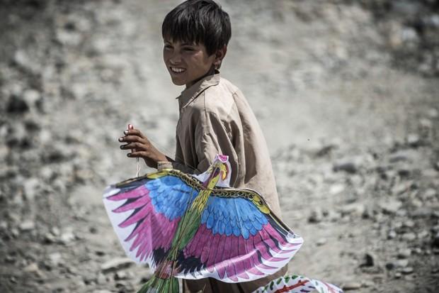 Menino carrega seu brinquedo novo (Foto: JEFF PACHOUD/AFP)