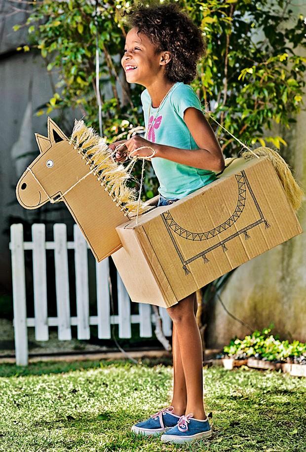Clara se diverte como cavalo de caixas de papelão comcrina e rabo de sisal (Foto: Iara Venanzi / Editora Globo)