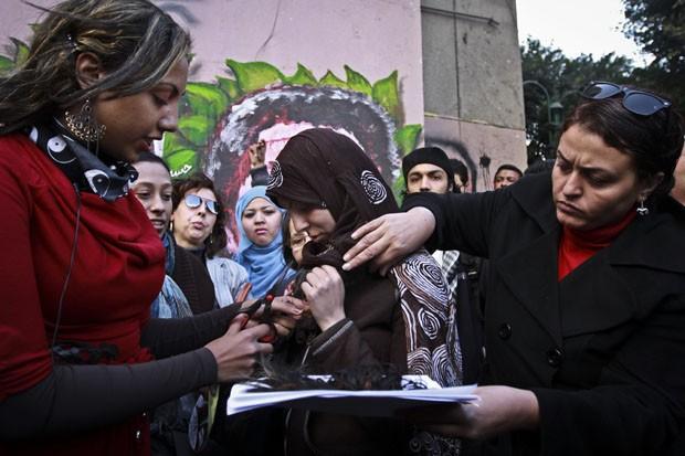 Mulher corta mecha de cabelo sem tirar o lenço da cabeça (Foto: Ahmed Abd El Latef/AP)