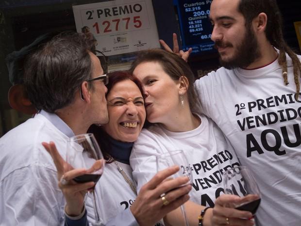 Cristina Ruiz, segunda à esquerda, 53, é parabenizada na frente de uma lotérica ao lado de outros proprietários, depois de vender o segundo prêmio de loteria de Natal 'El Gordo' em Logroño, norte da Espanha (Foto: AP/Alvaro Barrientos)