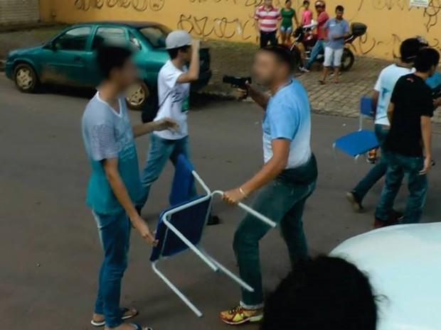 Suposto PM aponta arma para estudante durante protesto, em Goiás (Foto: Divulgação/Facebook)