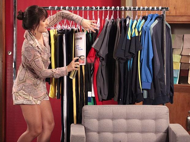Carolina borrifa o líquido nas roupas da Positano (Foto: Guerra dos Sexos / TV Globo)