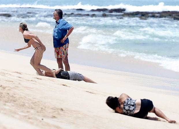 Após ajudar uma das babás, a modelo vai buscar água observada pelo pai, Gunther (de azul) (Foto: Grosby Group)