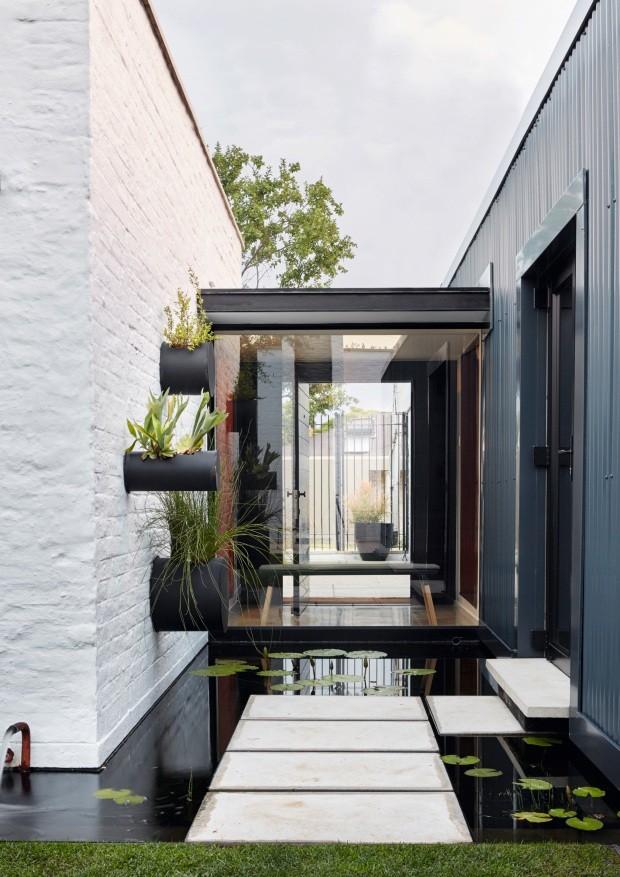 """Fundos. A parte """"antiga"""" da casa foi revestida de zinco ondulado. A alvenaria nova foi deixada exposta. A lareira ao ar livre proporciona aconchego ao jardim (Foto: Greg Cox / Bureaux.CO.ZA)"""