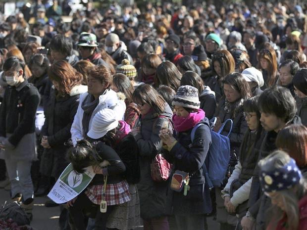 Japoneses fazem silêncio durante 1 minuto, a partir das 2h46 desta terça-feira (11), em Tóquio, em memória dos cerca de 19 mil mortos e desaparecidos após o potente terremoto e devastador tsunami que varreram o nordeste do Japão há 3 anos.  (Foto: Eugene Hoshiko / AP Photo)