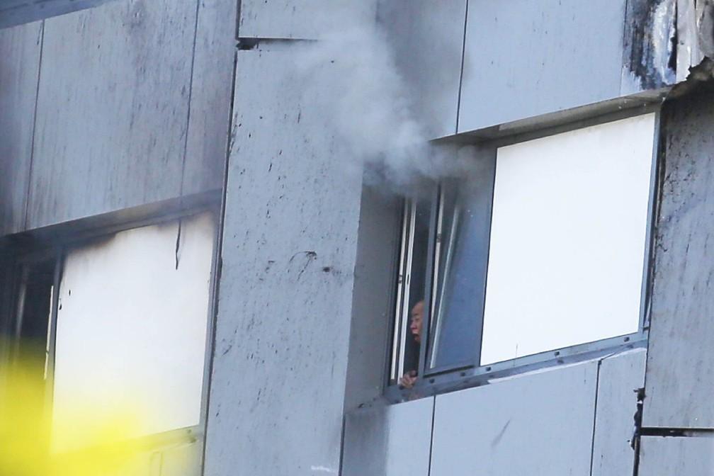 Pessoa é vista tossindo à janela do prédio em chamas enquanto fumaça sai do alto em Londres (Foto: Daniel Leal-Olivas/AFP)