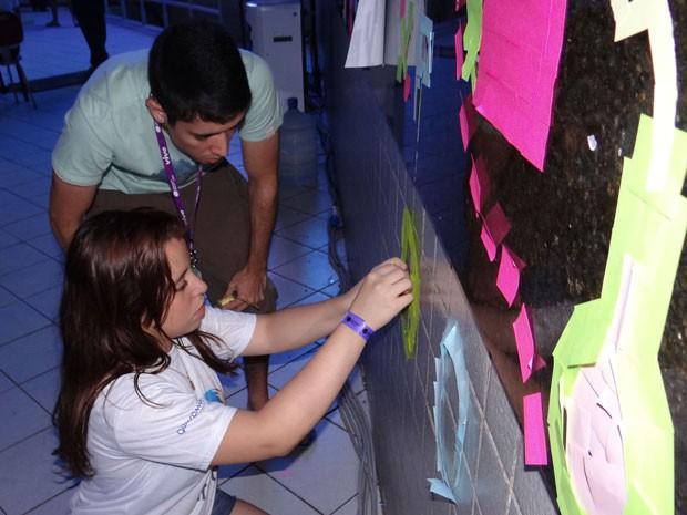 A estudante Camila Marinho, de 18 anos, e o namorado, o estudante Pedro Torres, de 20, fazem arte com post-it na Campus Party (Foto: Katherine Coutinho / G1)
