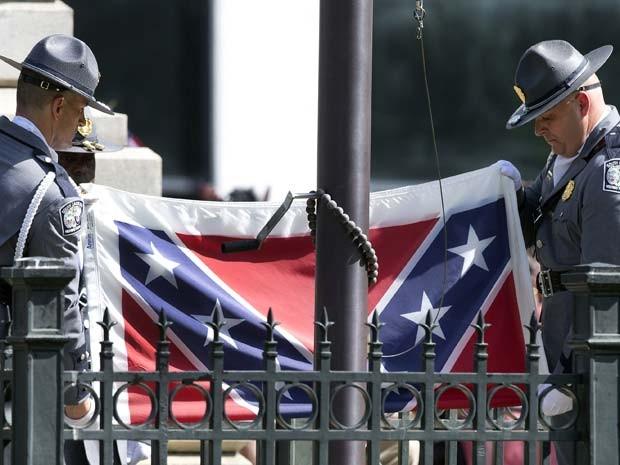 Guardas retiram bandeira confederada dos jardins do Capitólio da Carolina do Sul nesta sexta-feira (10) (Foto: AP Photo/John Bazemore)