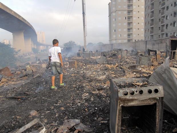 Garoto caminha em local destruído por um incêndio ocorrido ontem na Favela Portelinha da Penha, zona leste de São Paulo. Cerca de 90% das moradias foram consumidas pelo fogo (Foto: Cristiano Novais/CPN/Estadão Conteúdo)