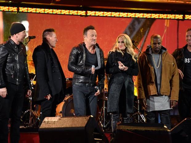 The Edge, Larry Mullen Jr., Bruce Springsteen, Carrie Underwood, Kayne West e Chris Martin em show na Times Square, em Nova York, nos Estados Unidos (Foto: Timothy A. Clary/ AFP)