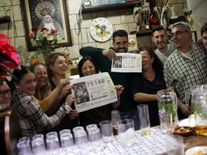 Alguns dos ganhadores do primeiro prêmio da loteria de Natal 'El Gordo' exibem o número sorteado, 79140, em Villanueva de la Concepción, na terça (22) (Foto: Reuters/Jon Nazca)
