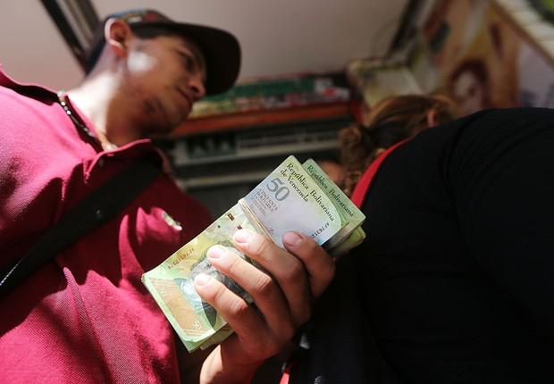 Trabalhador tenta trocar bolivares - a moeda nacional da Venezuela - pela moeda colombiana para comprar alimentos (Foto: Mario Tama/Getty Images)