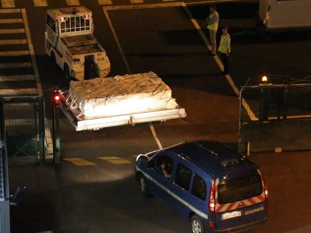 Policiais acompanham o embarque de peça encontrada na Ilha Reunião e que pode pertencer a um Boeing 777, na noite de sexta (31). O objeto será analisado por peritos franceses (Foto: AFP Photo/Richard Bouhet)