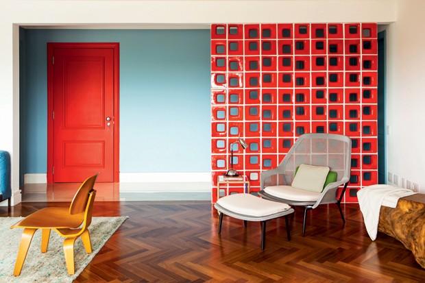 ESCONDE-ESCONDE: Para disfarçar a porta do lavabo, a equipe do escritório Patrícia Martinez Arquitetura idealizou uma divisória executada com cobogós Quadratto, da Elemento V. O vermelho, em contraste com o azul da parede, cria um espaço singular. (Foto: Edu Castello/Editora Globo)