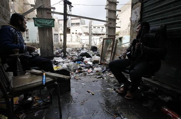 Rebelde sírio em rua devastada pelos combates na cidade de Allepo nesta terça-feira (29) (Foto: AFP)