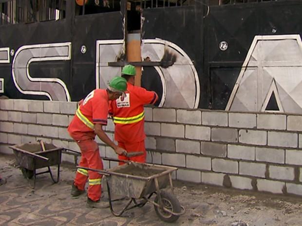 Funcionários da Prefeitura colocam blocos na entrada da sede da Gaviões da Fiel (Foto: TV Globo/Reprodução)