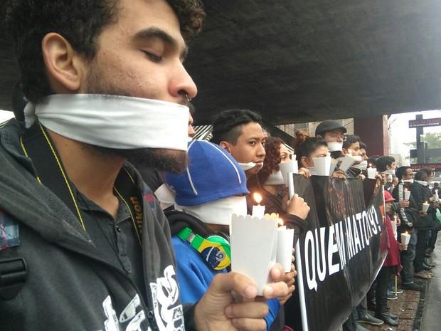 Amordaçados, manifestantes seguram velas em protesto contra chacina  (Foto: Carolina Dantas/ G1)