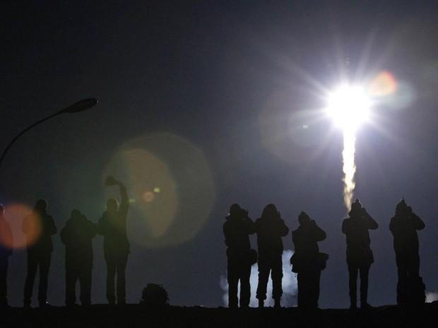 Pessoas observam de longe a decolagem da Soyuz TMA-12M, no cosmódromo de Baikonur, Cazaquistão. Dois cosmonautas russos e um astronauta americano partiram rumo à Estação Espacial Internacional (ISS) na tarde desta terça-feira (25) a bordo da nave russa. (Foto: Maxim Shemetov/Reuters)