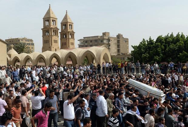 Egípcios carregam neste domingo (7) caixões de cristãos mortos (Foto: Khaled Desouki/AFP)