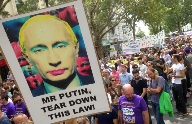 Manifestantes carregam cartazes com o rosto de Putin e recados anti-homofobia neste sábado (31), em Berlim (Foto: Gero Breloer/AP)