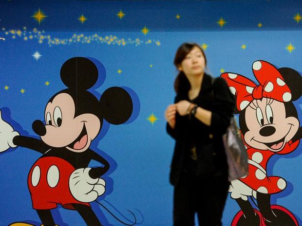 Mulher passa em frente a anúncio da Disneylândia de Hong Kong (Foto: AFP Photo/Philippe Lopez )