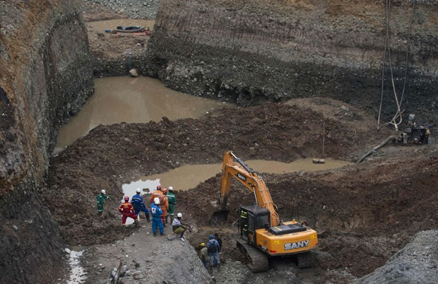 Equipe de resgate cava na mina ilegal na tentativa de resgatar os corpos dos mineiros (Foto: Luis Robayo/AFP)