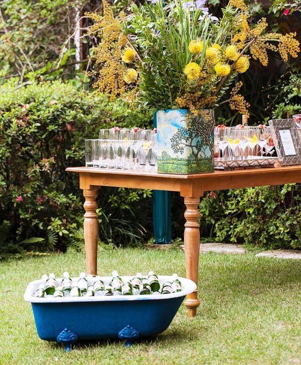Para um festão ao ar livre, arrume várias taças e flores em uma mesa de madeira.  Ao lado, coloque um minibanheira com bastante gelo e bebidas. A hora de se servir será uma diversão à parte. (Foto: Elisa Correa/Editora Globo)