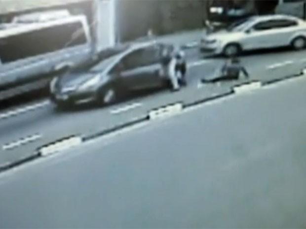 Mulher foi jogada pelo bandido no canteiro da via (Foto: TV Globo/Reprodução)