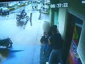 Funcionários mobilizam assaltante enquanto outro foge de motocicleta em Araguaína (Foto: Reprodução/TV Anhanguera)