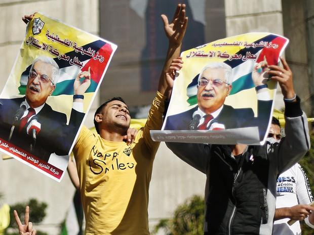 29 de novembro - Palestinos segurar cartazes do presidente Mahmoud Abbas, durante uma manifestação de apoio aos esforços para garantir um upgrade diplomática nas Nações Unidas, na Cidade de Gaza  (Foto: Suhaib Salem/Reuters)