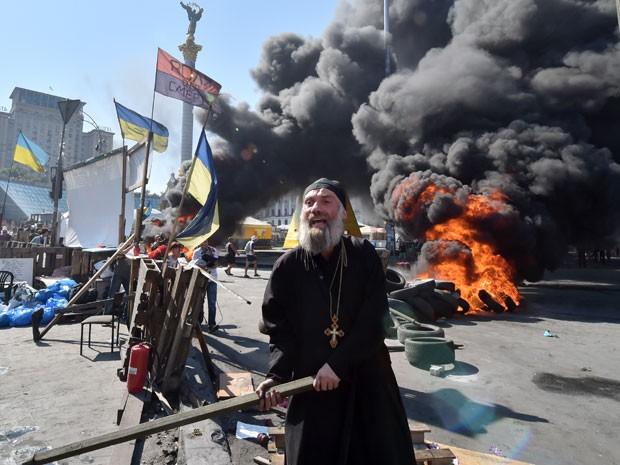 Sacerdote ortodoxo segura um pedaço de pau durante confronto em praça de Kiev (Foto: Sergei Supinski/AFP)