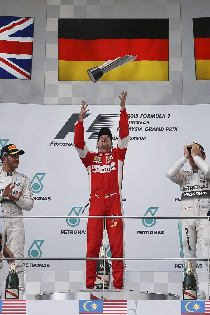 Sebastian Vettel celebra vitória no GP da Maláisa, enquanto Lewis Hamilton e Nico Rosberg se mostram desconfortáveis no pódio (Foto: EFE)