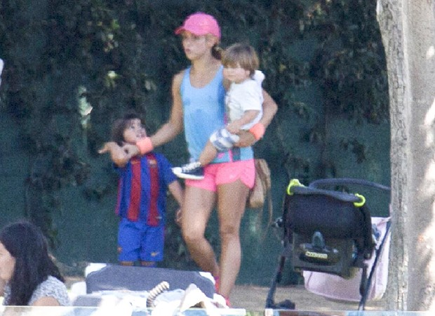Shakira com os filhos Sasha, no colo, e Milan, com uniforme do Barcelona (Foto: Grosby Group)