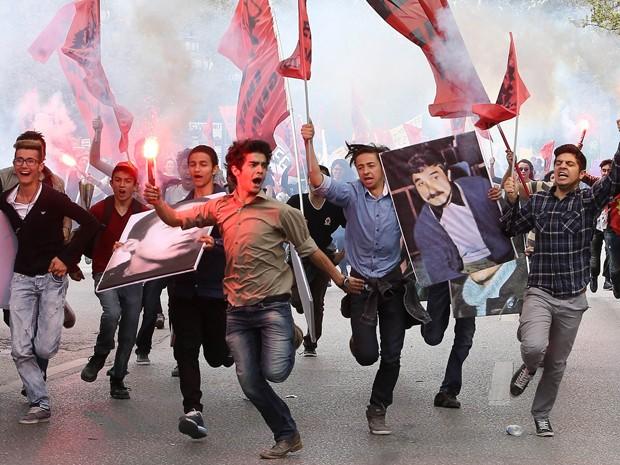 Manifestantes correm, carregando retratos de ativistas de 1968 durante uma manifestação do Dia do Trabalho na praça Sihhiye, em Ankara, na Turquia (Foto: AFP Photo/Adem Altan)