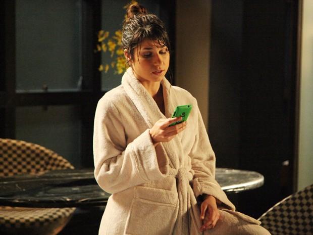 Manu vê ligação de Megan e pensa em atender (Foto: Carol Caminha/ TV Globo)