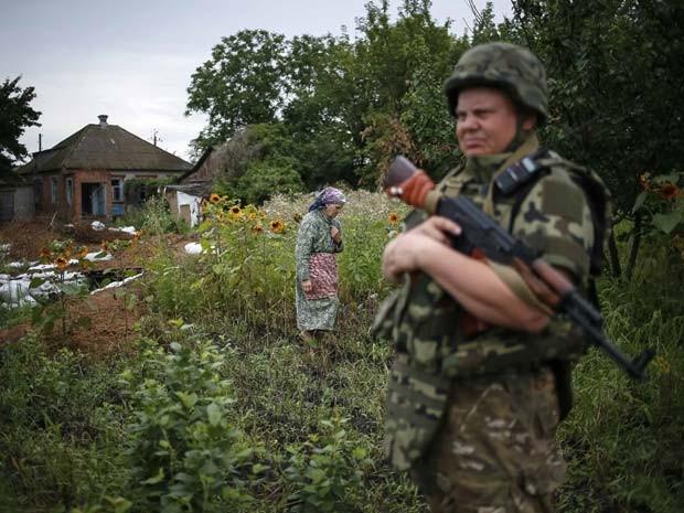 Membro da força-tarefa especial da polícia da Ucrânia patrulha vila Semenovka, perto da cidade de Sloviansk, no leste da Ucrânia nesta segunda-feira (14) (Foto: REUTERS/Gleb Garanich)