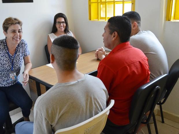 A assistente social Letícia Barros e a psicóloga Simone Gonzales conversam com Fernando e os filhos (Foto: Adriano Oliveira/G1)