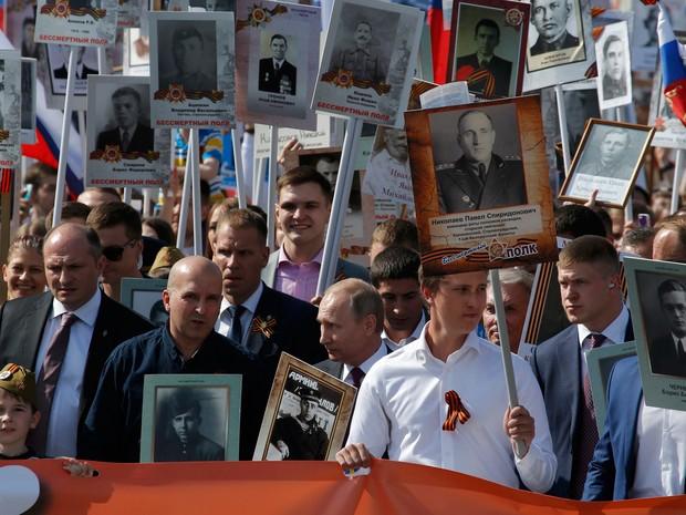 Presidente russo, Vladimir Putin, segura retrato de seu pai durante as celebrações do Dia da Vitória em Moscou (Foto: Sergei Karpukhin/Reuters)