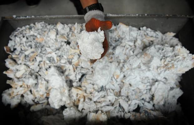Marfim de elefante incinerado é remexido por funcionário do Escritório de Vida Selvagem e Áreas Protegidas das Filipinas, nesta quarta-feira (26). Mais de cinco toneladas do produto que haviam sido apreendidas pelo governo filipino estão sendo destruídas (Foto: Noel Celis/AFP)
