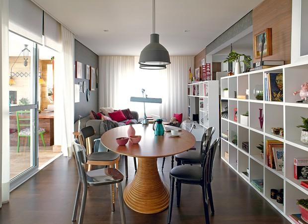 a sala de jantar tem mesa oval de Fernando Jaeger, cadeiras de diferentes estilos da Micasa e é composta da estante de nichos vazados de mesmo tamanho (38cm de largura x 34 cm de altura), que percorre toda a sala (Foto: Victor Affaro)