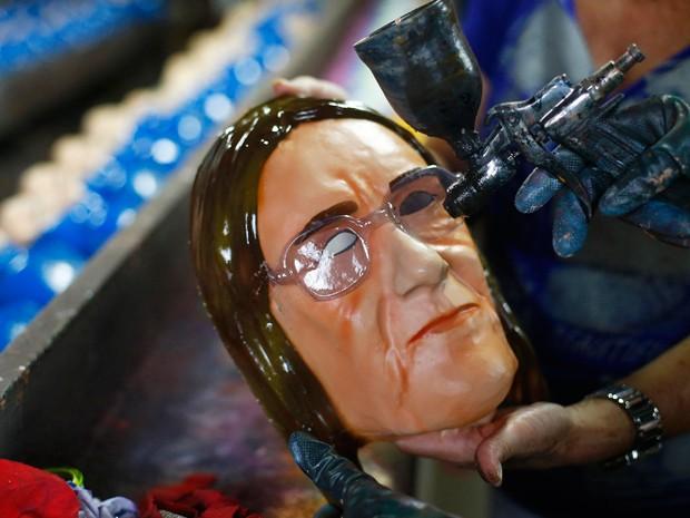Funcionário da fábrica dá os últimos retoques na máscara inspirada em Graça Foster (Foto: Reuters)
