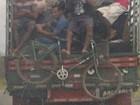 Homens se deslocam na carroceria de um caminhão, entre cadeiras