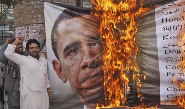 Paquistanês queima foto de Obama durante protesto por passagem de combio da Otan no país, na sexta (Foto: Arshad Butt / AP)