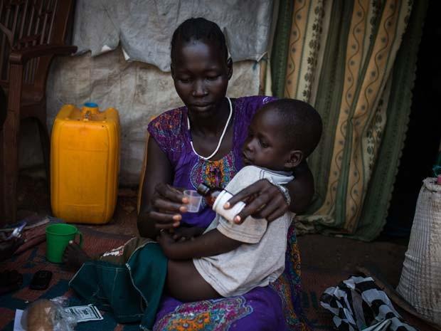Mulher dá remédio para filho em campo para deslocados internos em Juba, no Sudão do Sul; conflito que eclodiu em dezembro de 2013 no país forçou o deslocamento de mais de 1.5 milhões de pessoas (Foto: UNHCR / A. McConnell)