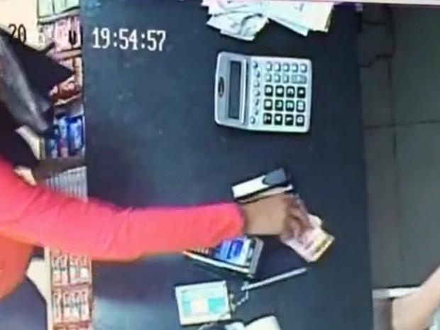 Assaltante pega dinheiro de caixa durante assalto a padaria em Jales (Foto: Divulgação/Polícia Militar)