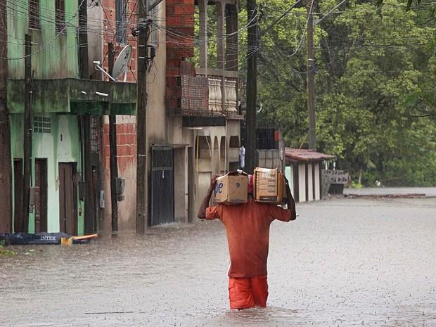 Homem atravessa área alagada levando mantimentos em Serra, no Espírito Santo. (Foto: Flávio GSouza/Futura Press/Estadão Conteúdo)