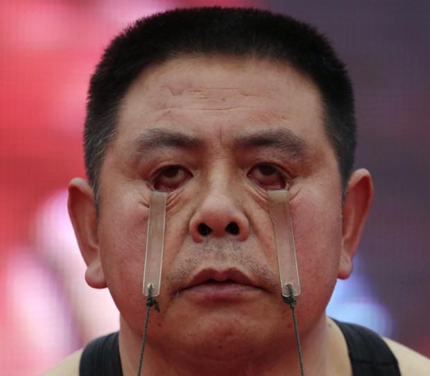 Wang ergueu dois baldes por um minuto apenas usando as pálpebras (Foto: Reuters)